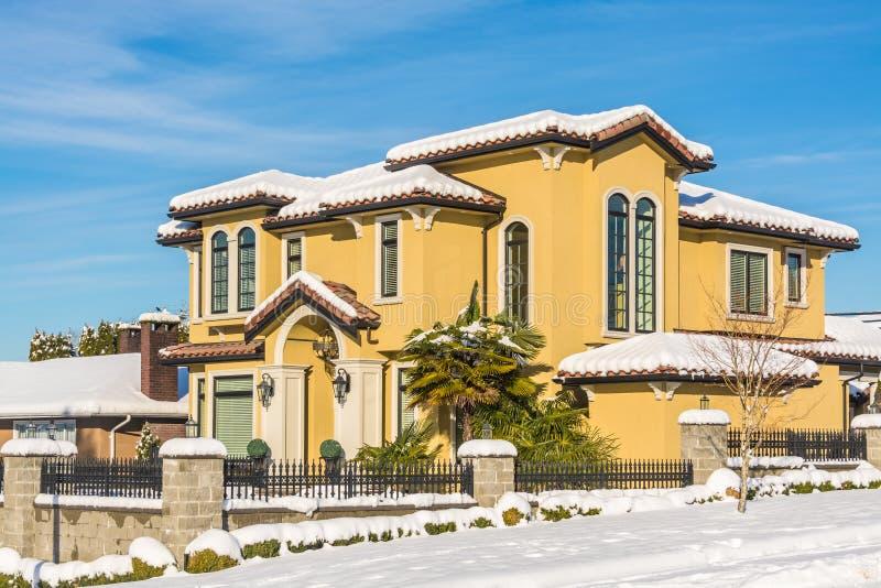 Maison résidentielle luxueuse dans la neige le jour ensoleillé d'hiver au Canada image libre de droits