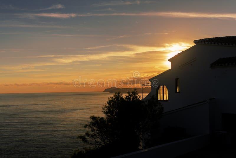 Maison reculée avec un toit carrelé par la mer au coucher du soleil Javea Spane images stock