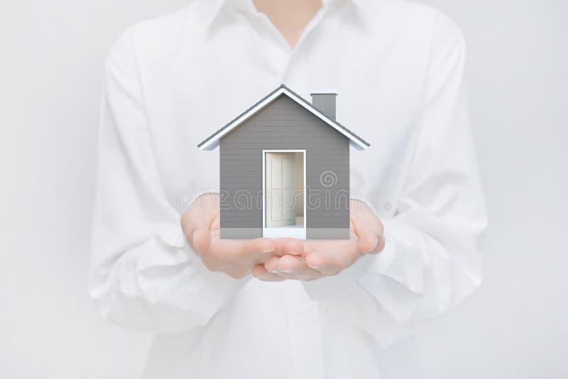 Maison simple dans des mains humaines Idée d'image de concept d'immobiliers et de propriété illustration libre de droits