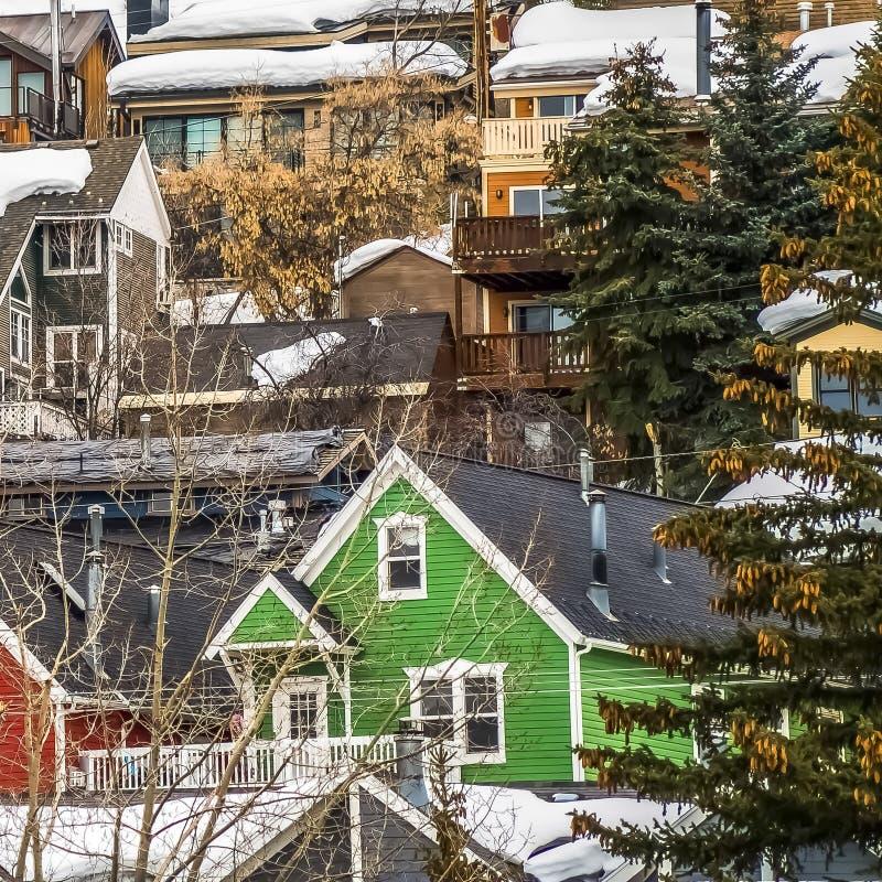 Maisons carrées avec les murs extérieurs colorés construits sur la montagne avec la neige épaisse en hiver image libre de droits