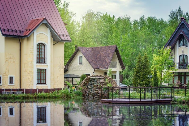 Maisons de luxe priv?es par le lac dans la for?t au ressort pluvieux ?galisant le temps image libre de droits