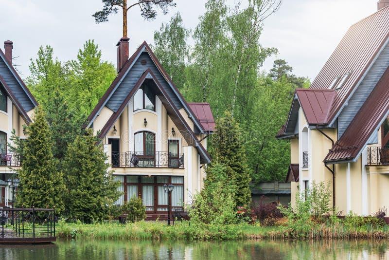 Maisons de luxe priv?es par le lac dans la for?t au temps pluvieux de journ?e de printemps photographie stock