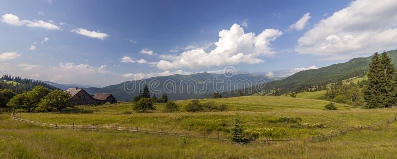 Maisons de village sur des collines avec les prés verts dans le jour d'été photos libres de droits