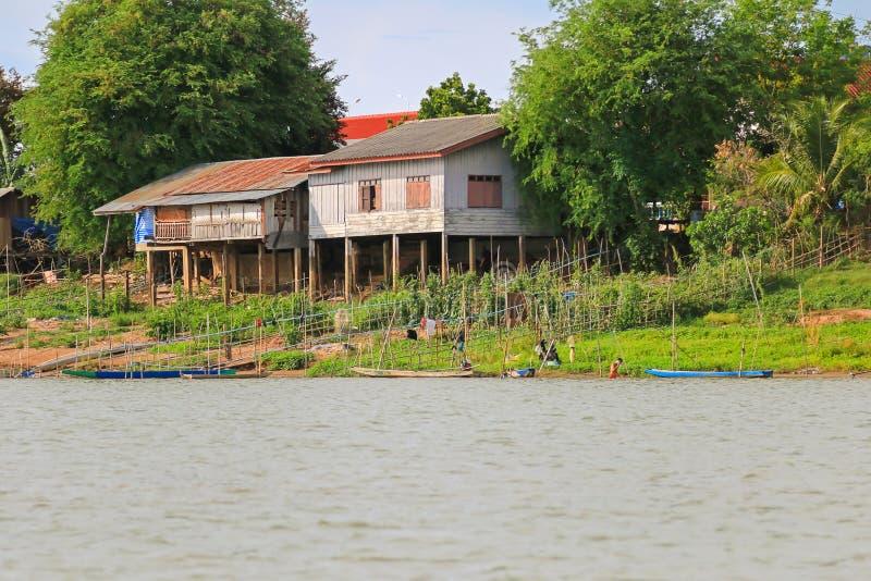Maisons en bois sur les poteaux concrets le long de la rive du Mekong, images stock