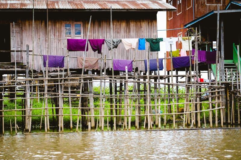 Maisons en bois traditionnelles sur le lac Inle avec sécher les vêtements colorés photographie stock