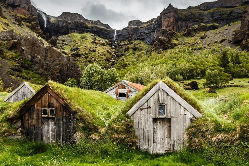 Maisons islandaises de gazon et canyon rocheux avec la cascade au CCB images libres de droits
