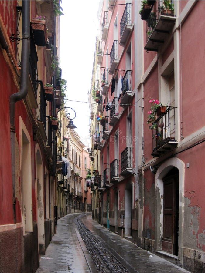 Maisons roses de Cagliari Longue rue de ville menant à la mer photos stock
