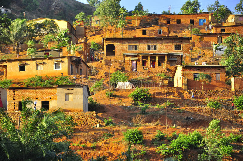 Maisons rouges de boue dans un village dans la jungle africaine image libre de droits