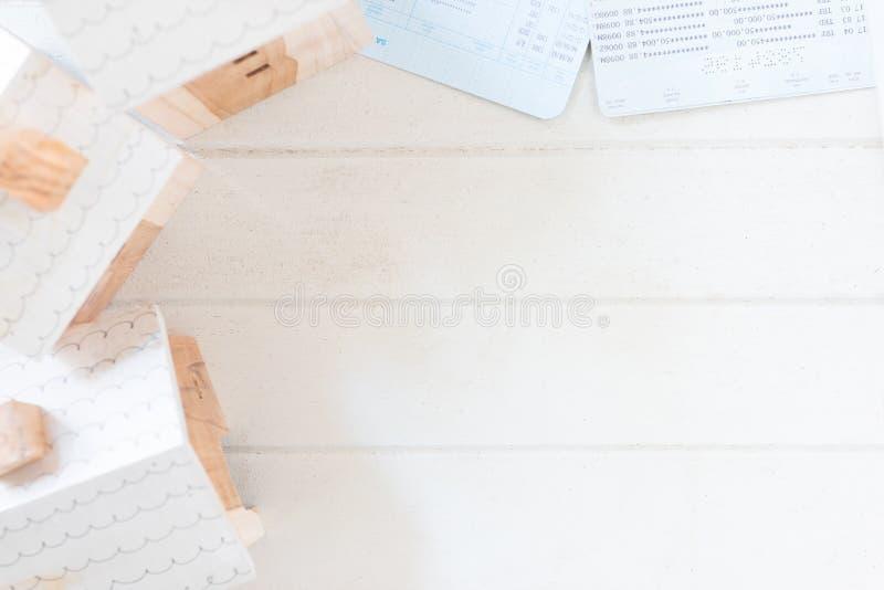 Majątkowa inwestycja, miniatura domu model z obrachunkową książką na białej drewno desce zdjęcia royalty free