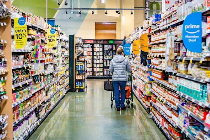 Maj 17, 2019 Cupertino/CA/USA - sikten av en gång i ett Whole Foods lager, Amazon Primemedlem erbjuder synligt på hyllorna; royaltyfri fotografi