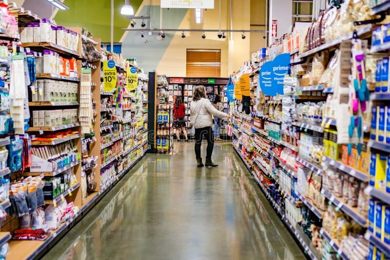Maj 17, 2019 Cupertino/CA/USA - sikten av en g?ng i ett Whole Foods lager, Amazon Primemedlem erbjuder synligt p? hyllorna; royaltyfri fotografi