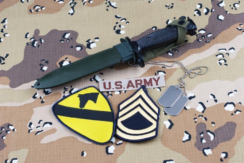 Maj 12, 2018 Etiketter för bajonett och för hund för lapp för uppdelning för kavalleri för USA-ARMÉ 1st på ökenkamouflagelikformi arkivbild