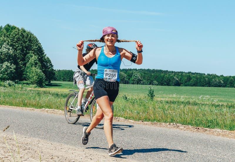 Maj 26-27, 2018 Naliboki, Białoruś Belarusian maratonu Naliboki A amatorska kobieta biega przy cyklista na drodze obrazy royalty free