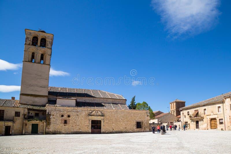 Maj 2019, Pedraza, Castilla Y Leon, Spanien: turister nära Iglesia San Juan Bautista i Plazaborgmästare royaltyfri bild