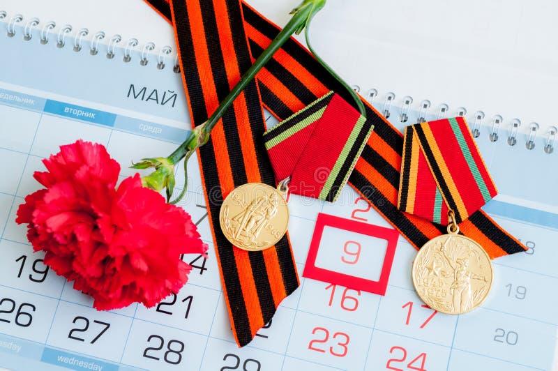 9 Maj - röd nejlika med det krigmedaljGeorge bandet som ligger på kalendern med 9 det Maj datumet royaltyfri bild