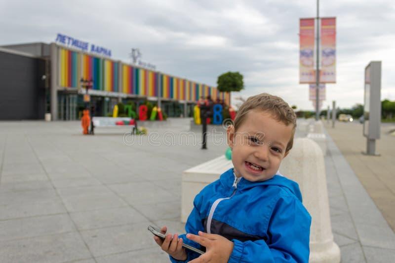 Maj 24, 2019 w Varna, Bułgaria chłopiec obsiadanie na kamiennej ławce przed Śmiertelnie 2 przy Varna lotniskiem międzynarodowym obraz stock