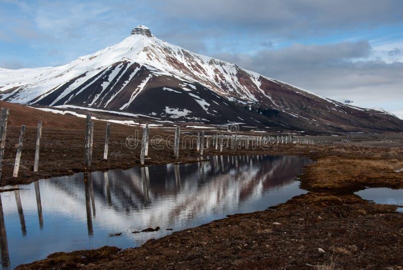 Majesctic Pyramida berg som står högt över den övergav ryska spökstaden Pyramiden i Svalbard arkivfoton