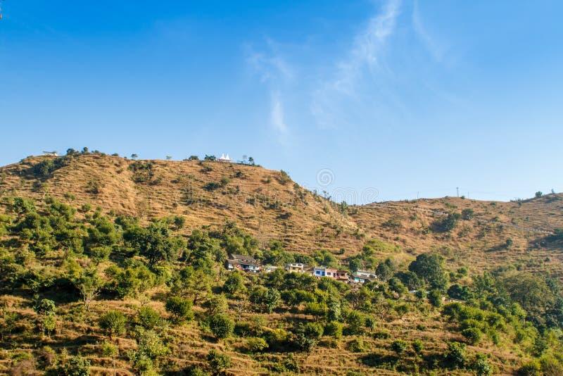 Majestätische Morgenberglandschaft mit buntem Wald und blauem Himmel Kleine Häuser und grüne Bäume auf Inder Himalaja stockfoto