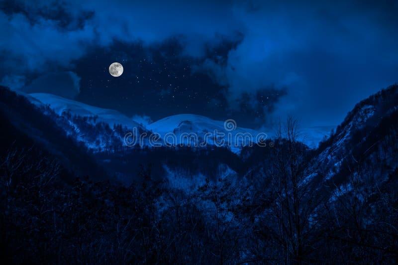 Majestätische Winternacht in einem Gebirgstal mit Vollmond in einem sternenklaren Himmel stockfoto