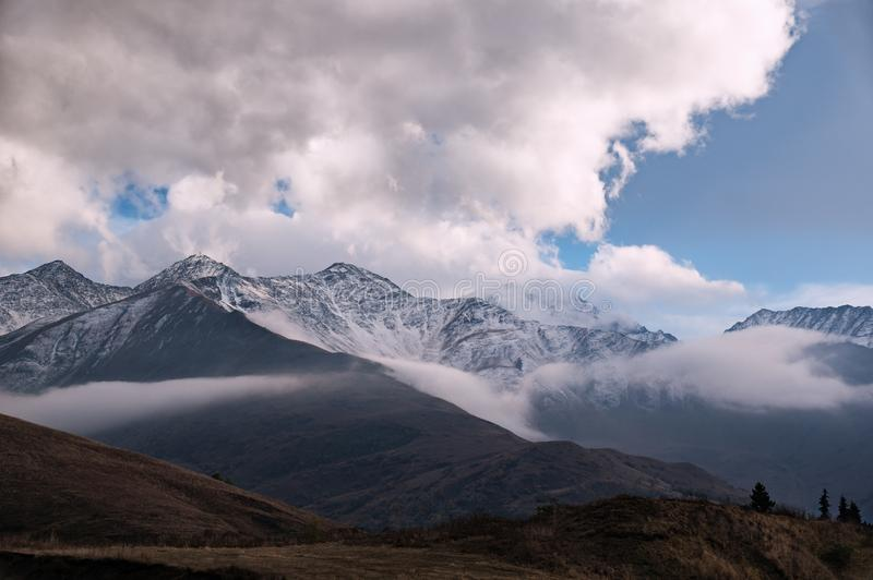 Majestätischer Bergblick - felsige Spitzen umfasst mit Schnee auf dem Horizont mit einigen dunkelbraunen Herbsthügeln in der Fron lizenzfreie stockfotos