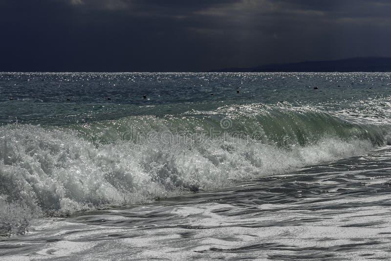 Majestätischer Türkis und grünes Schwellen mit den Sonnenlichtreflexionen, die in einen Strand an einem Sommertag des blauen Himm stockfotografie