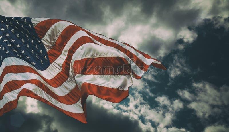 Majestätisk Förenta staternaflagga mot en mörk bakgrund royaltyfri fotografi