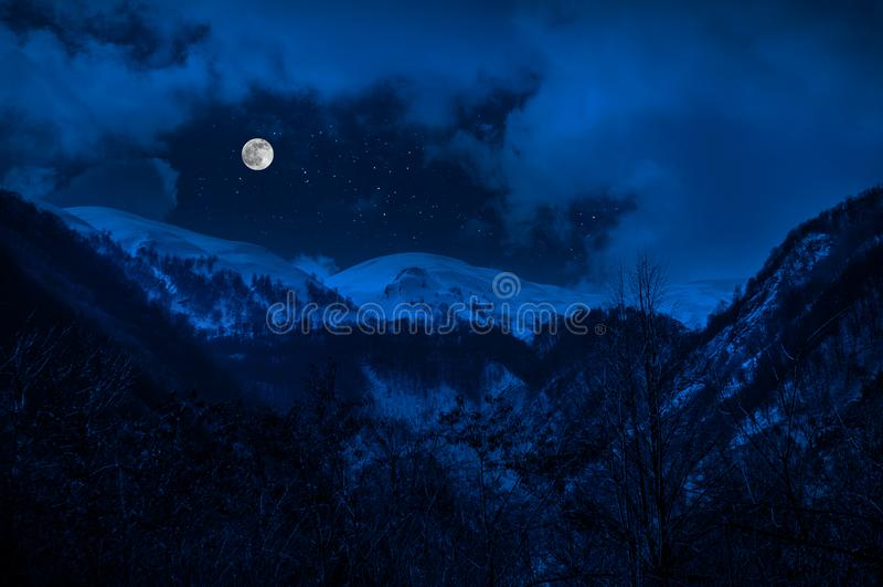 Majestätisk vinternatt i en bergdal med fullmånen i en stjärnklar himmel arkivfoto