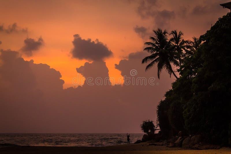 Majestätiska moln och orange himmel på solnedgången över det indiska havet royaltyfria bilder