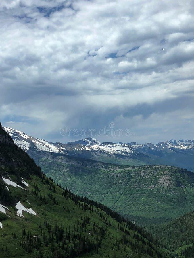 Majestätiska snöig berg med molnig himmel fotografering för bildbyråer