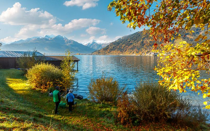 Majestic Autumn Moring on the Zeller Lake, Austria. Father and son are fishing. Active and healthy lifestyle. The concept of the upbringing of children, a royalty free stock images