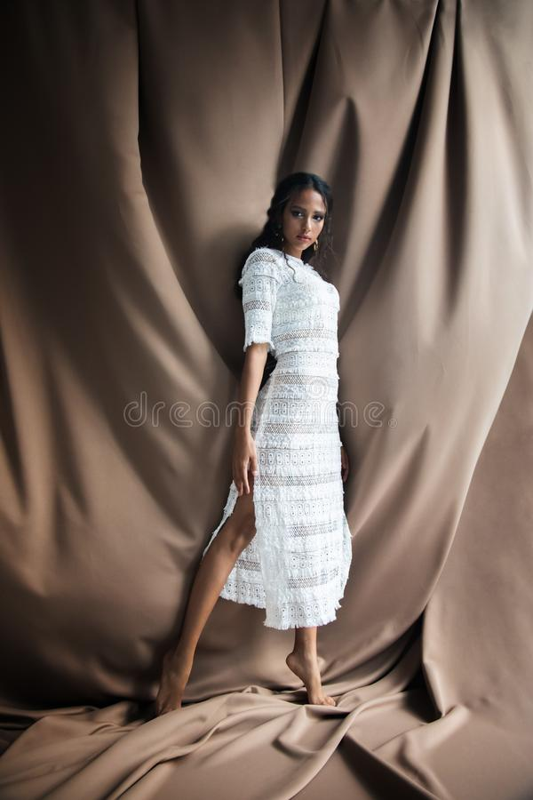 Majestic Beautiful Barefooted Mulatto Girl. In white lacy dress posing on chocolate textile texture background stock photo