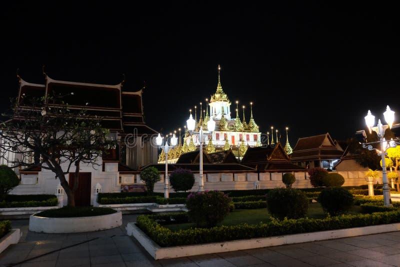 The majestic Buddhist temple in Bangkok at night. Street lights illuminate the small garden.  stock photos
