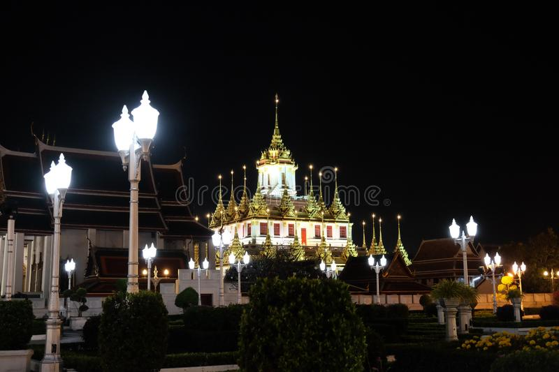 The majestic Buddhist temple in Bangkok at night. Street lights illuminate the small garden.  royalty free stock image