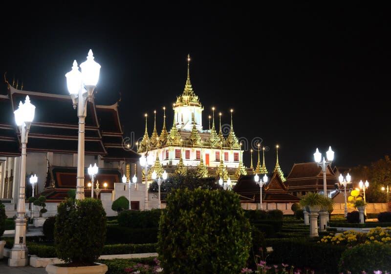 The majestic Buddhist temple in Bangkok at night. Street lights illuminate the small garden.  stock photo