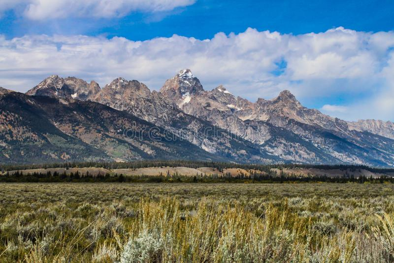 Majestic Grand Teton Mountains with beautiful blue skies. And bright white fluffy clouds royalty free stock image