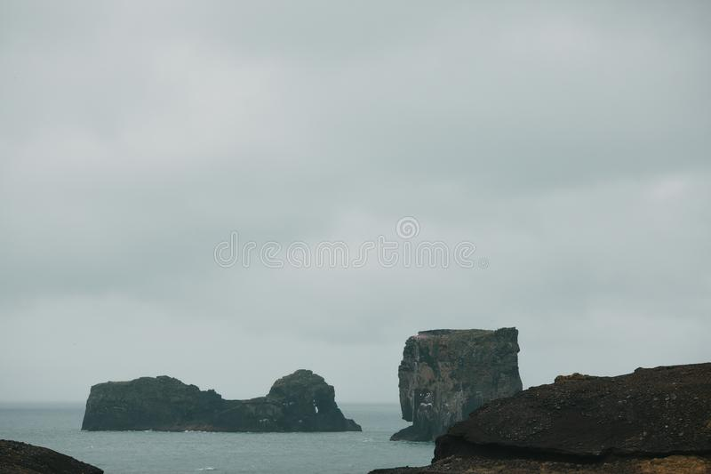 Majestic icelandic landscape with cliffs in ocean and cloudy sky, vik dyrholaey, reynisfjara. Beach, iceland stock photos