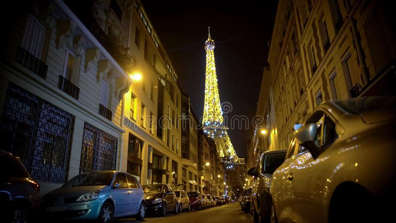 Majestic illuminated Eiffel Tower sparkling at night, view from narrow street royalty free stock photo