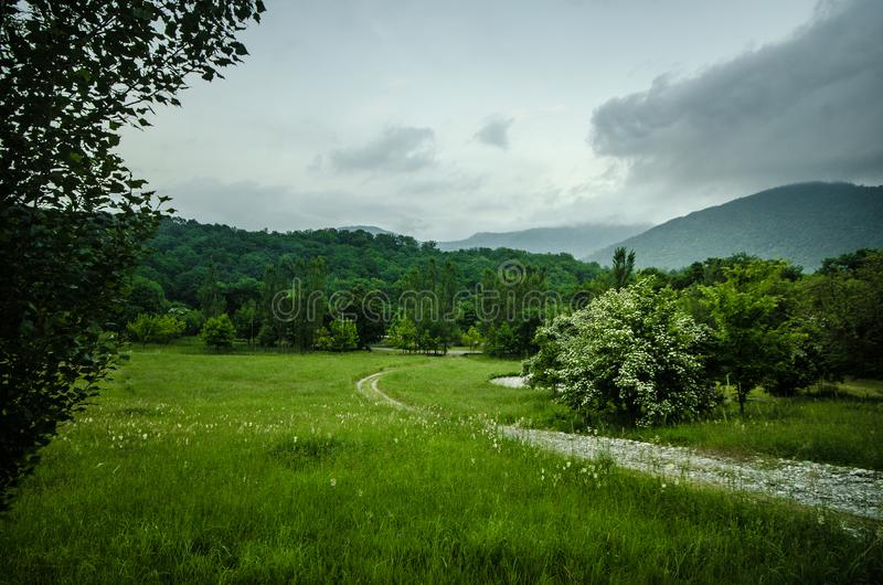 Majestic landscape of mountains and Meadow. Cycling mountain road. Misty mountain road in high mountains.. Cloudy sky with mountai royalty free stock images