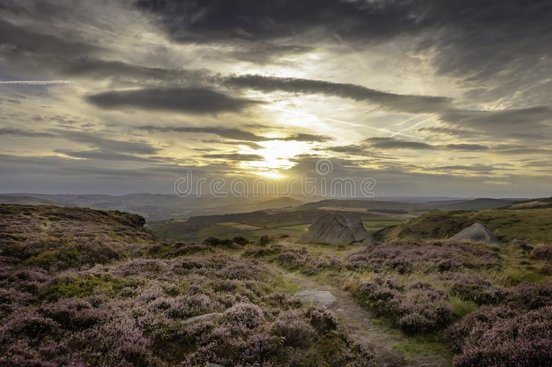 Majestic landscape of Peak District National Park, Derbyshire, Uk. Sunset over moorland covered with purple heather flowers in summer and dramatic sky above stock photography