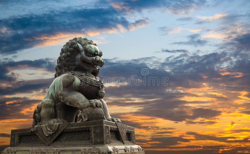 Majestic lion statue with sunset glow background stock image
