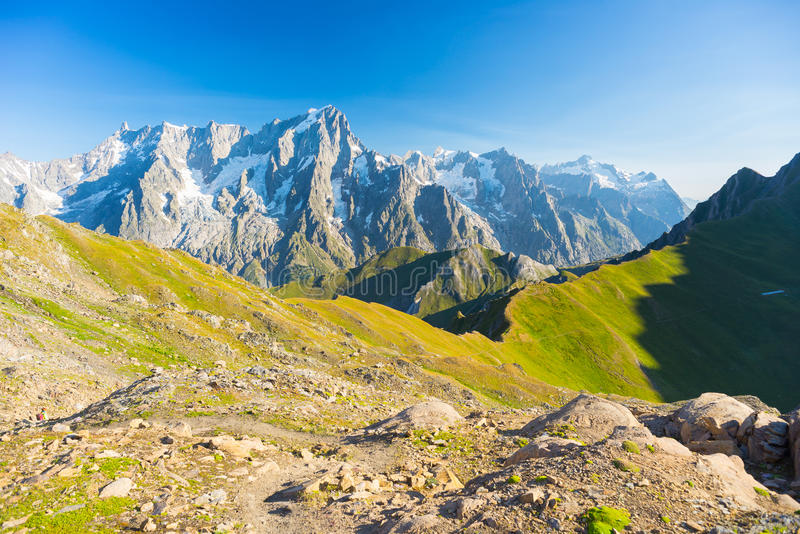Majestic Mont Blanc massif and lush green alpine valley. Hih mountain trail with great panoramic view over the Mont Blanc massif. Backpacker's summer adventures royalty free stock photography