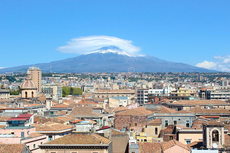 Majestic Mount Etna overlooking the Sicilian city Catania, Italy. Smoke cloud over the famous volcano, snow on the top. Dominant stock image