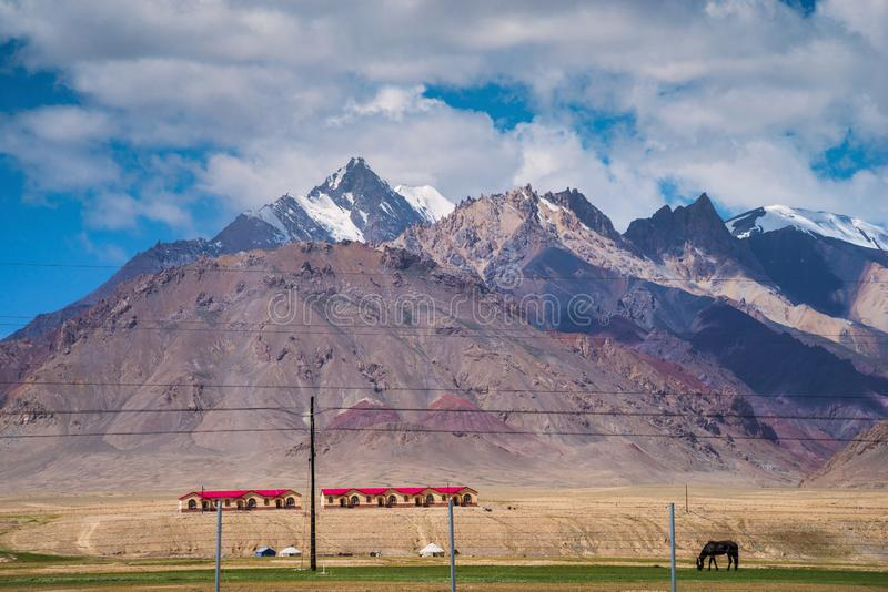 Majestic mountains and horse on meadows in Pamirs plateau. Majestic snow-capped mountains peak with cloudy blue sky in Pamirs plateau,alone black horse grazing stock photography