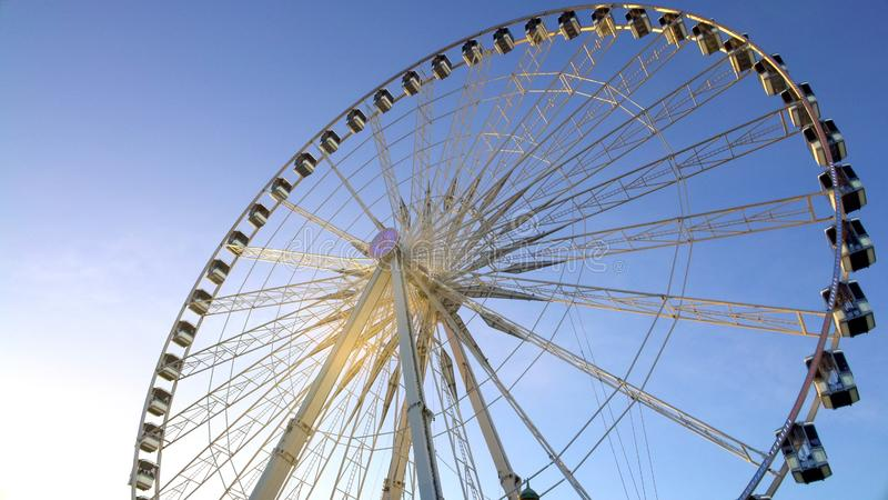 Majestic observation wheel rotating in amusement park, sunny blue sky background royalty free stock photography