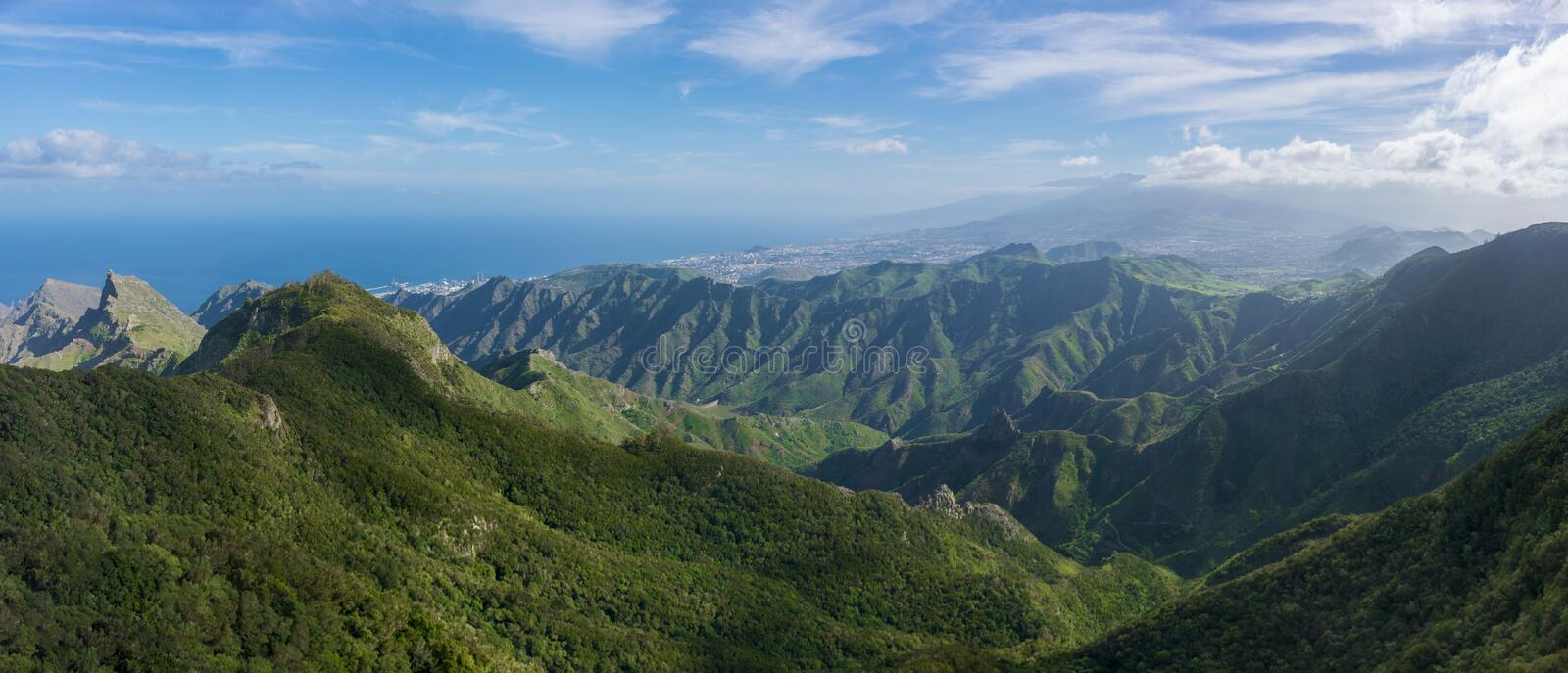 Majestic panoramic view of the Roques de Anaga. Beautiful mountain range and green valley with ocean on the background. royalty free stock photography