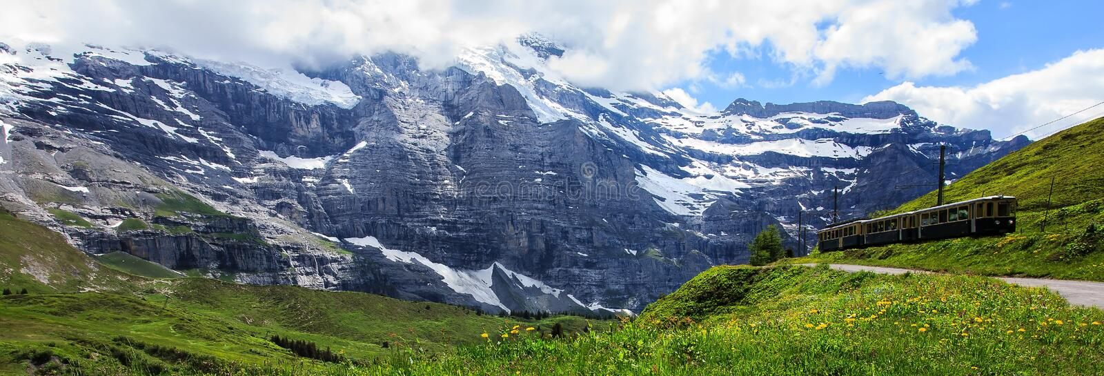Majestic panoramic view of scenery along a swiss railways train, connecting Kleine Scheidegg to Wengernalp stations, Switzerland stock photography