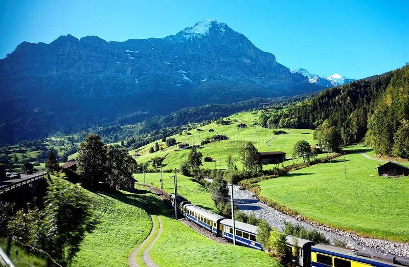 Majestic scenery of Grindelwald village, with view of an alpine train traveling on the green grassy hill. & the famous Eiger North Face in Jungfrau region stock images