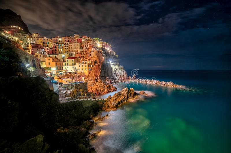 Majestic shot of the turquoise ocean and the lighted coastline of colorful buildings at nighttime. A majestic shot of the turquoise ocean and the lighted stock image