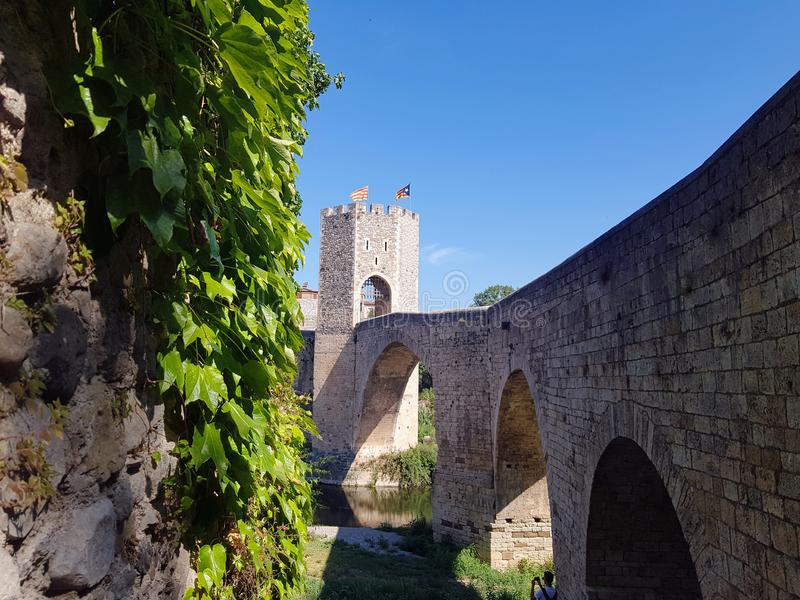 Majestic stone arched bridge in Besalu - famous medieval village Catalonia, Spain. Amazing atmospheric place for tourism near Me. Majestic stone arched bridge in royalty free stock photography
