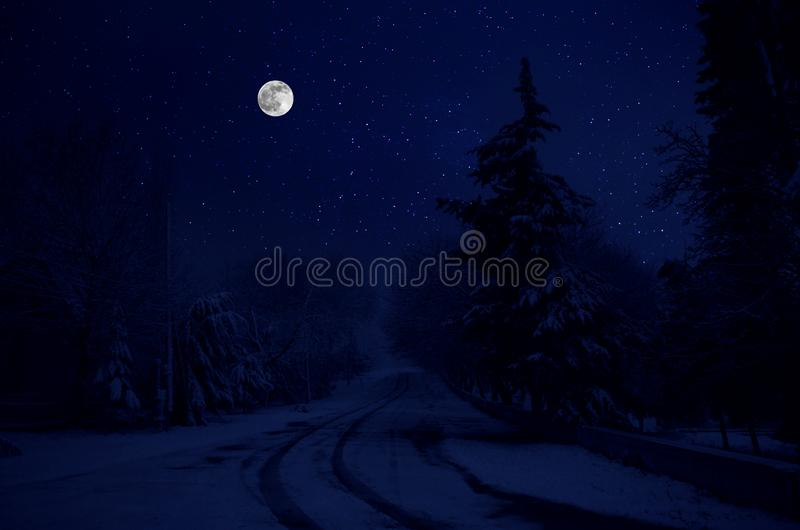 Majestic winter night in a mountain valley with full moon in a starry sky. Beautifulsnowy night landscape with moon royalty free stock photo
